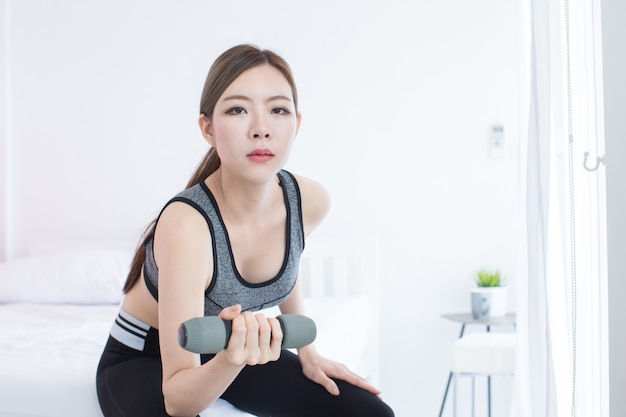 Young asian beautiful fitness girl  lifting dumbbell in room