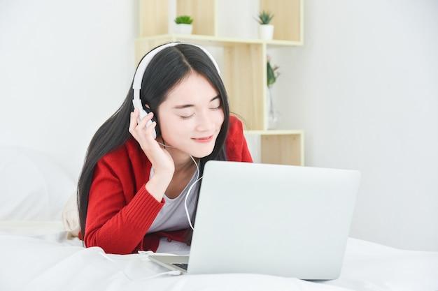 젊은 아시아 아름 다운 소녀 침대에 누워 헤드폰을 통해 노트북 컴퓨터에서 음악을 듣고