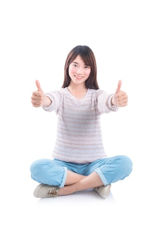 Young asian beautiful girl sitting on the floor and showing thumbs up over white background
