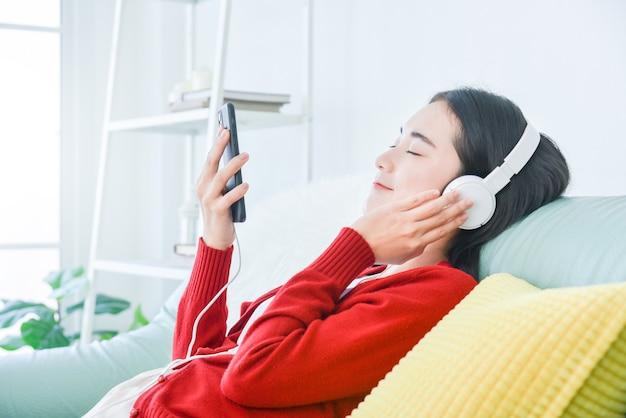 젊은 아시아 아름 다운 소녀 소파에 앉아 헤드폰을 통해 스마트 폰에서 음악을 듣고