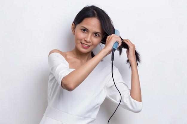 白の縮毛矯正器で髪をまっすぐにする若いアジアの美しい幸せな女性