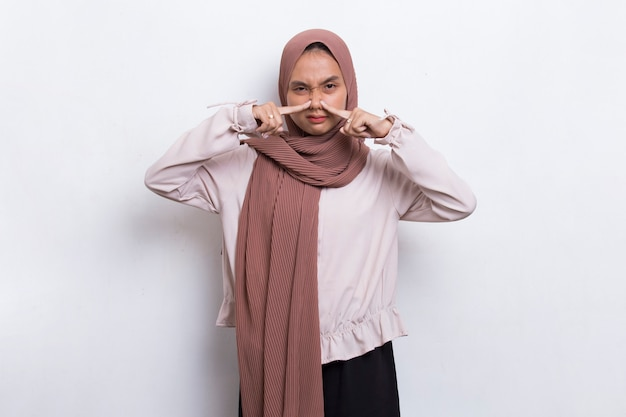 Young asian beautiful muslim woman holding her nose because of a bad smelling something