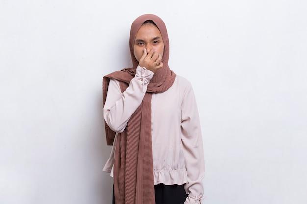 나쁜 냄새 때문에 코를 잡고 있는 젊은 아시아 아름다운 이슬람 여성