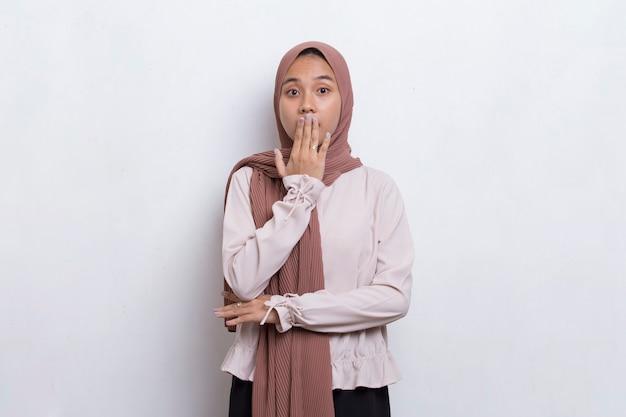 Молодая азиатская красивая мусульманская женщина шокирована, прикрывая рот руками за ошибку секретная концепция