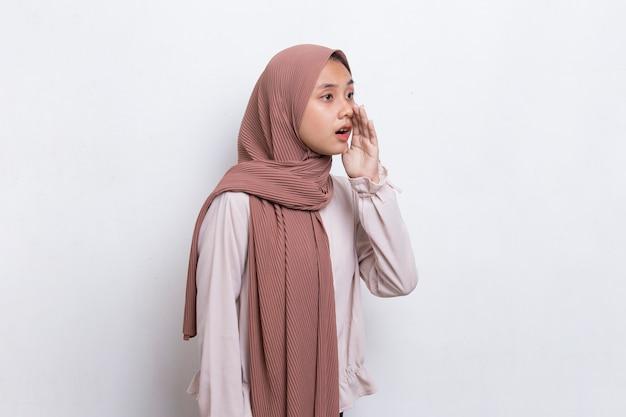 若いアジアの美しいイスラム教徒の女性の叫び声と叫び声が白い背景で隔離のアナウンス