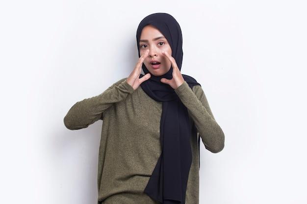 젊은 아시아의 아름다운 이슬람 여성이 흰색 배경에 격리되어 소리를 지르며 고함을 지른다