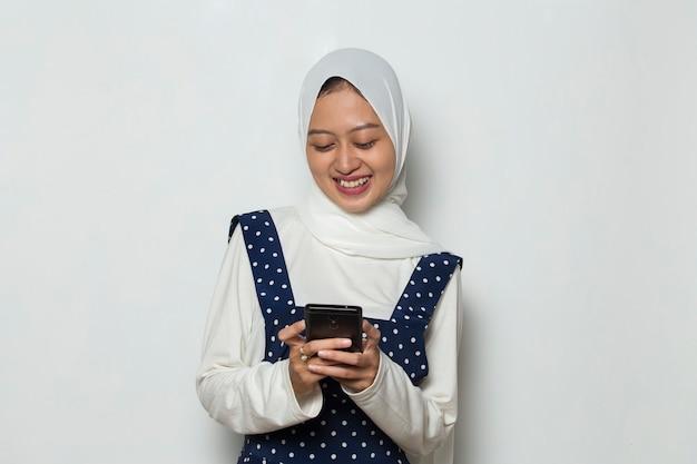 Young asian beautiful muslim woman using mobile phone