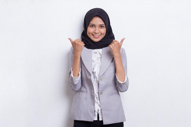 Молодая азиатская красивая мусульманская женщина с одобренным жестом знака вверх изолирована на белом фоне