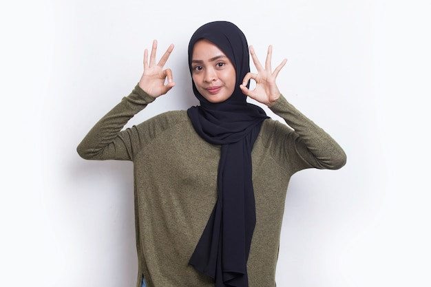 흰색 배경에 격리된 확인 표시 제스처를 가진 젊은 아시아 아름다운 이슬람 여성