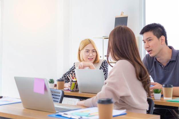 彼女の同僚がオフィスのテーブルに座っている彼女の話を聞いている間、ジェスチャーをして何かを話し合っている若いアジアの美しい女性