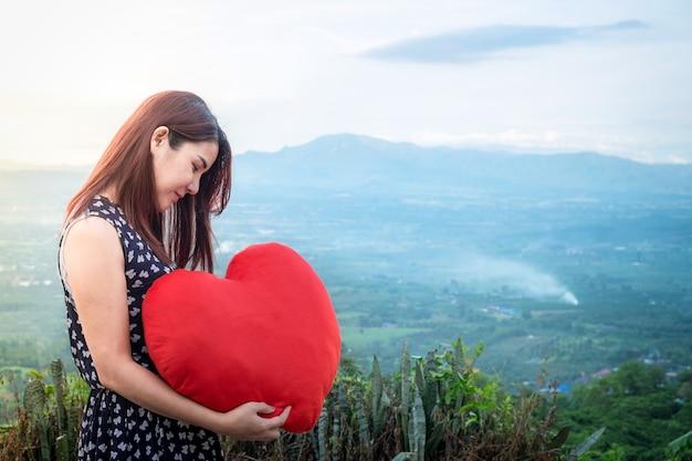 マウンテンビューの背景に手に大きな赤い心を保持している若いアジアの美しい女性