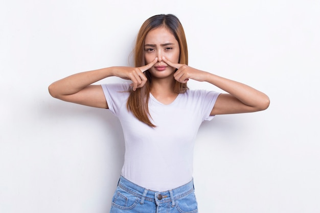 Young asian beautiful woman holding her nose because of a bad smelling something