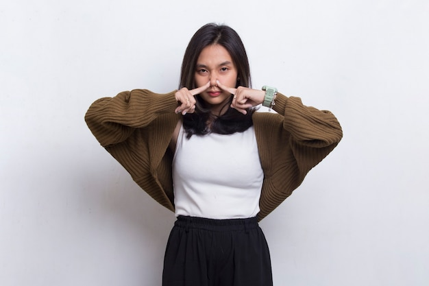 何か臭いが悪いので彼女の鼻を保持している若いアジアの美しい女性