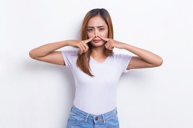 나쁜 냄새 때문에 코를 잡고 있는 젊은 아시아 아름다운 여성