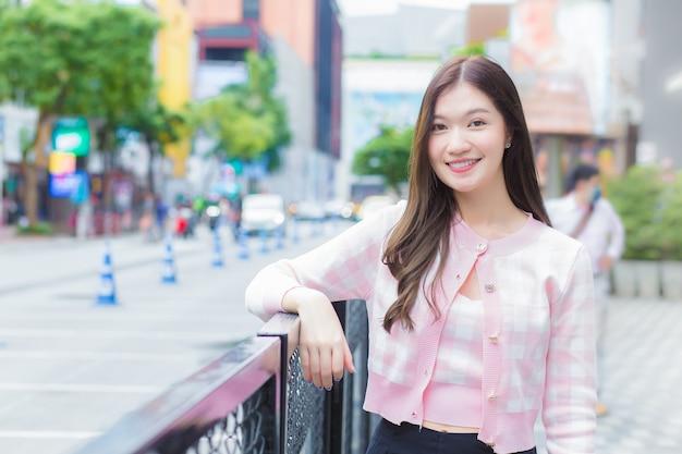 ピンクと白の縞模様のコートを着た若いアジアの美しい女性は、都市と都市の屋外に立っています