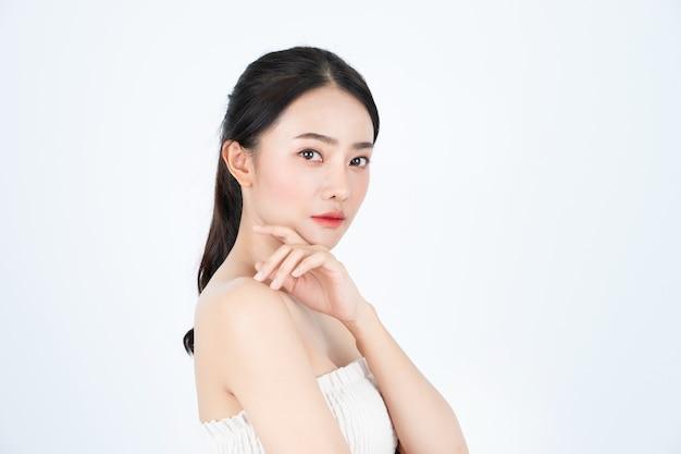 흰색 땀받이에 젊은 아시아 아름 다운 여자는 건강하고 밝은 피부를 가지고 있습니다.