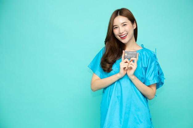 Молодая азиатская красивая женщина-пациент, держащая кредитную карту, изолированную на зеленом фоне