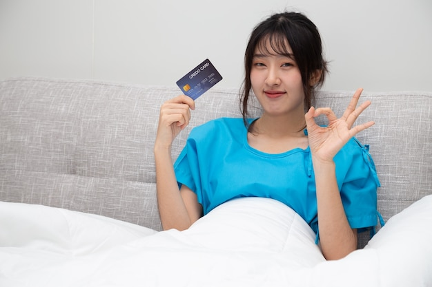 Young asian beautiful woman patient showing ok sign, credit card and sitting on bed, insurance policy by bank concept