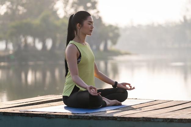 요가를 하고 연꽃 속에서 명상을 하는 젊은 아시아 여성은 휴식과 마음의 평화를 위해 아침에 호수 옆 야외에서 포즈를 취합니다. 조화와 명상 개념입니다. 건강한 생활
