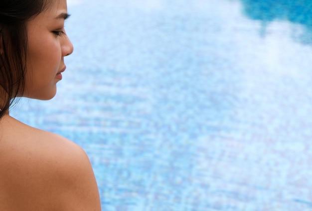 Молодой азии красивая женщина отдыха в бассейне на курорте