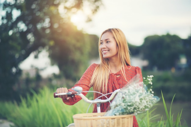 Young asian beautiful woman riding a bicycle in a park