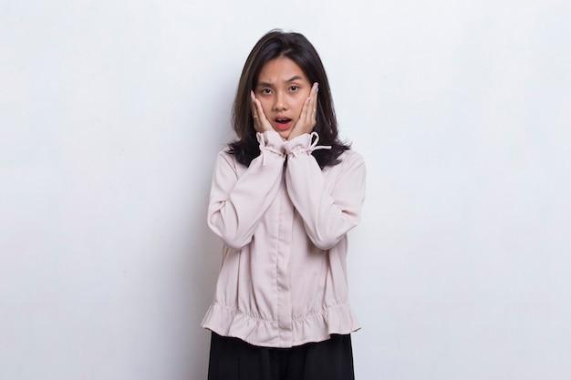 Молодая азиатская красивая женщина шокирована прикрывая рот руками за ошибку на белом фоне