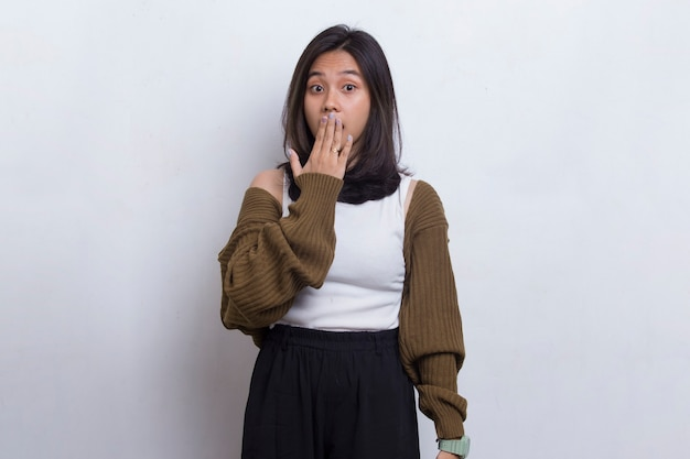 Young asian beautiful woman shocked covering mouth with hands for mistake on white background