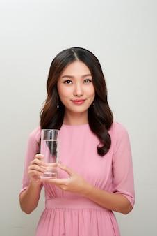 Молодая азиатская красивая женщина показывая стакан воды.