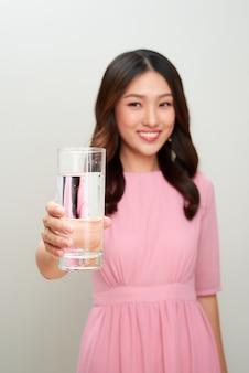 水のガラスを示す若いアジアの美しい女性。