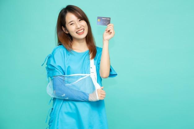 患者の服を着て、腕の骨折のために柔らかい副子を身に着けている若いアジアの美しい女性