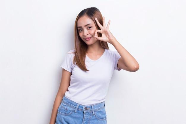 흰색 배경에 격리된 확인 표시 제스처를 가진 젊은 아시아 아름다운 여성