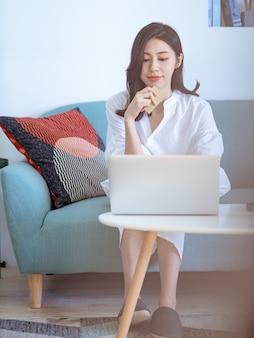 Молодая азиатская красота делает покупки онлайн с помощью кредитной карты и ноутбука дома