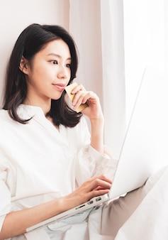 Молодая азиатская красота делает покупки онлайн с помощью кредитной карты и ноутбука