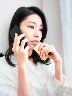 Молодой азиатский шоппинг красоты с мобильным телефоном и кредитной картой