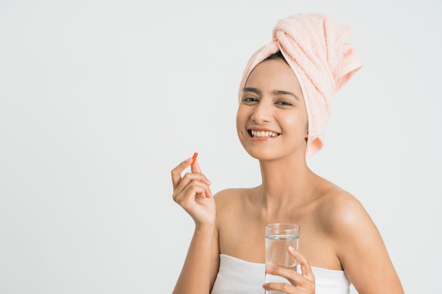 Young asian beauty young woman eating pills and drinking water on white wall.