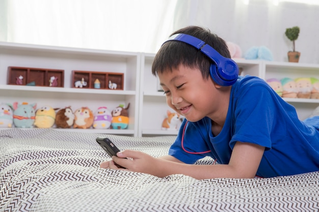 Young asian boy in blue headphones is smiling and listening to music on the bed at home