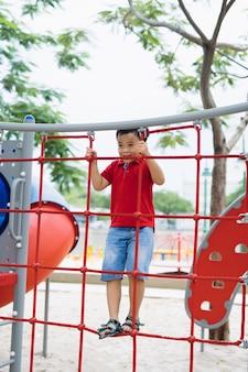 若いアジアの少年は、大きな木の下の屋外の遊び場で運動するために、赤いロープのフェンスと灰色のバーに手で登ります。