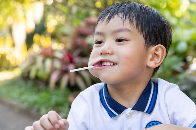 Young asian boy eating a lollipop