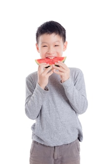 Young asian boy eating a slice of watermelon over white background