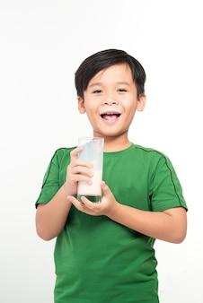 白でミルクのガラスを保持している若いアジアの少年