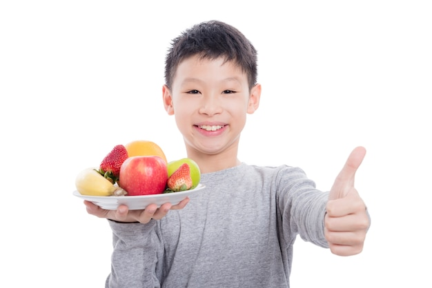 Young asian boy holding fruits and smiles over white background
