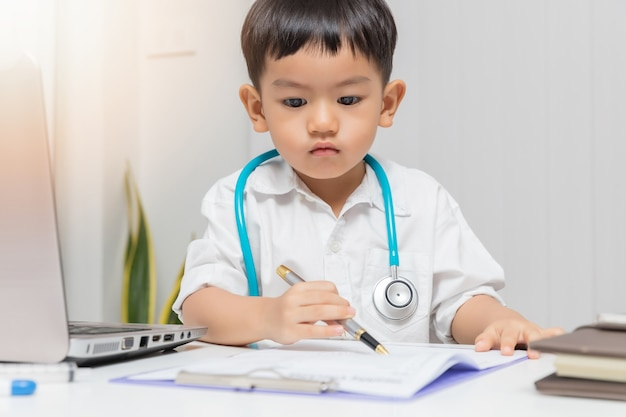 Young asian boy playing doctor and writing on diagnostic chart.