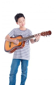 Young asian boy playing guitar and smiles over white background