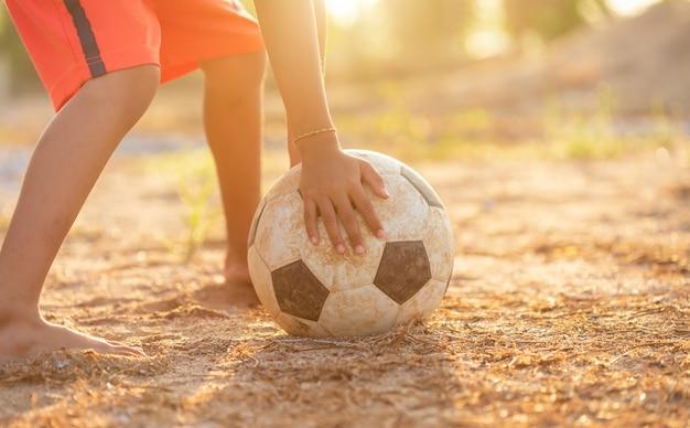 Молодой азиатский мальчик играя с старым и пакостным классическим футбольным мячом в утре