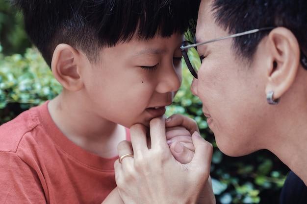 屋外の公園で彼の母親と一緒に祈っている若いアジア少年、家族の祈り