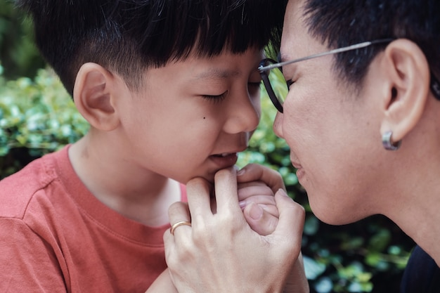Young asian boy praying with his mother in the park outdoors, family pray