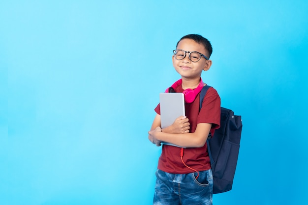 若いアジアの男子生徒、タブレットとカバンを保持しているタイの子供