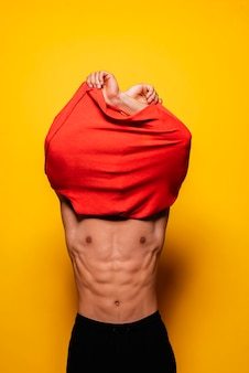 Young asian boy taking off the t-shirt. fitness body concept.
