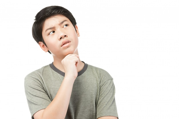 Young asian boy thinking and looking  upwards while smiling .