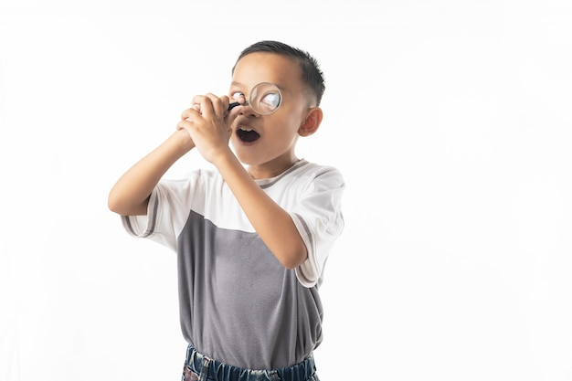 Young asian boy use magnifying glass, thai student isolated